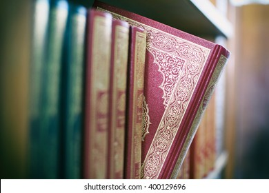 A book is selected from bookshelf in public library with vintage filter blur background