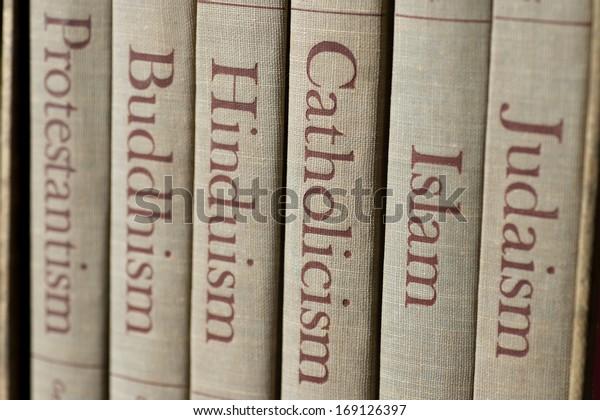 Книжные корешки перечисляют основные мировые религии - иудаизм, ислам, католицизм, индуизм, буддизм и протестантизм. В центре внимания — слово «католицизм».