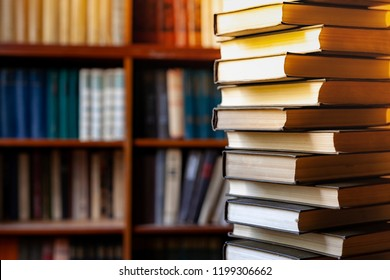 Book stack  blurred bookshelf in the library room, education background, back to school concept