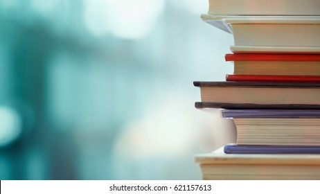 Photo of Book stack in the library room and blurred bookshelf for business and education background, back to school concept
