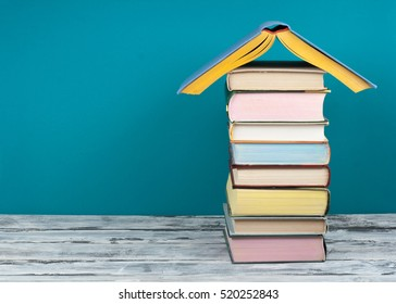 Book stacking. Open book, hardback books on wooden table and blue background. Back to school. Real estate concept, house shape. Copy space for text.