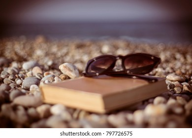 Book and sunglasses on the beach. Shallow depth of field.