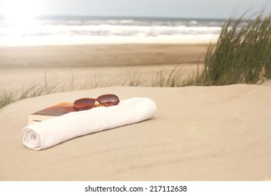 Book sunglasses and towel lying in the sand on the beach of the North Sea Denmark