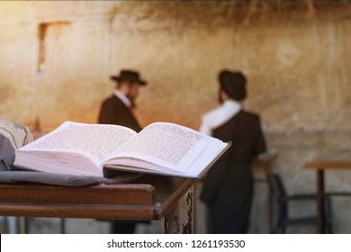 book of the Torah - Pentateuch of Moses is open on the prayer table on the background of praying Orthodox Jews. JERUSALEM, ISRAEL. 24 October 2018: