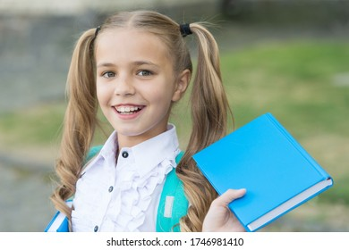 Book is uniquely portable magic. Happy schoolgirl hold book outdoors. Little reader. School library. Literature study. Reading habit. Book shop. Education and knowledge. Book you cant resist.
