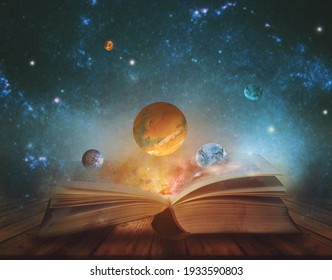 Book of the universe - opened magic book with planets and galaxies. Elements of this image furnished by NASA - Shutterstock ID 1933590803