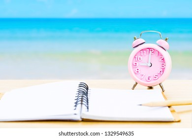 book and vintage clock with yellow on wooden platform beside tropical beach and blue sea on day noon light. back to school or summer camp fun party concept