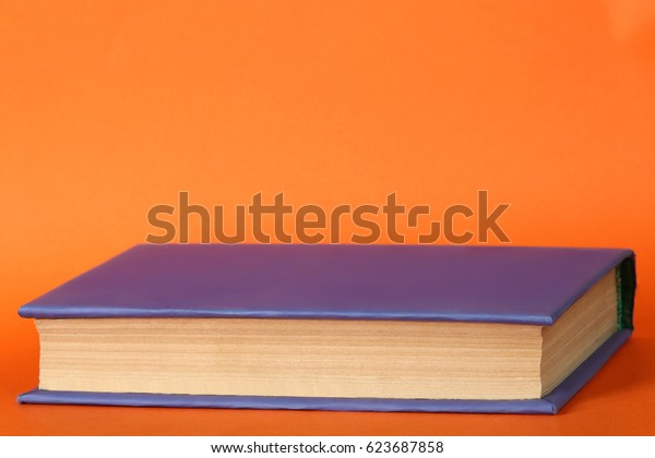 Book with a violet cover on an orange background