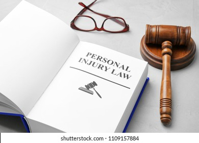 Book with words PERSONAL INJURY LAW, gavel and glasses on grey background