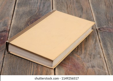 A book in yellow binding on a wooden background. Front view.