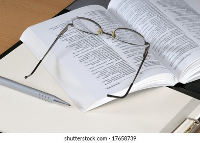 Book,glasses and pencil on an empty notepad