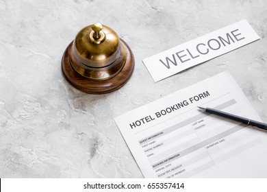 booking form for hotel room reservation, pen and ring stone background