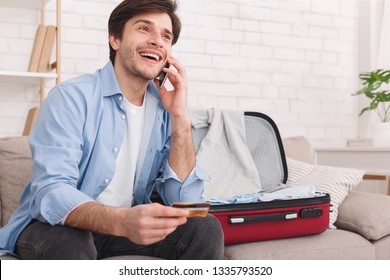 Booking hotel. Man talking on phone and holding credit card, preparing for vacation