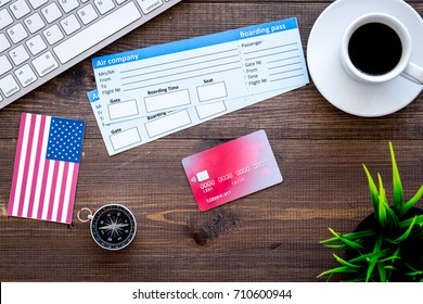 booking trip with tickets, flags and tourist outfit on wooden office desk background top view