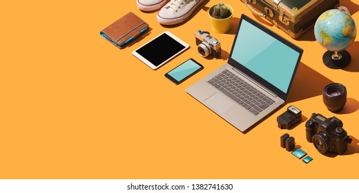 Booking vacations online, getting ready to leave and packing: laptop and travel accessories on a desktop