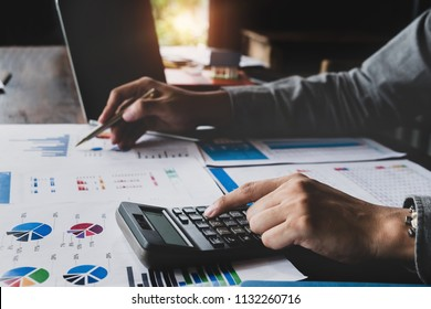 Bookkeeper accounting Concepts, Male use calculator, pen and computer laptop to monitor money saving reports budget to plan before retire. nspector accountant concept.