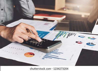 Bookkeeper accounting Concepts; Male use calculator, pen and laptop computer to monitor money saving reports budget to plan before retire. inspector accountant concept.