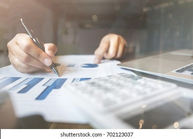 bookkeeper /  financial inspector calculating on investment data with documents and laptop in dark office room