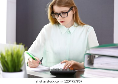 Bookkeeper or financial inspector woman making report, calculating or checking balance. Audit and tax service concept. Green colored image background