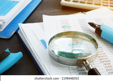 Bookkeeping and audit. Magnifying glass and business documents.