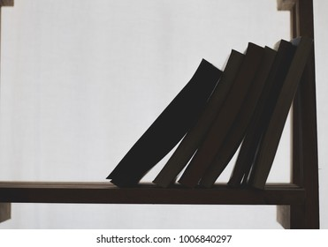 Booklets and books placed on shelves made of wood on white background.