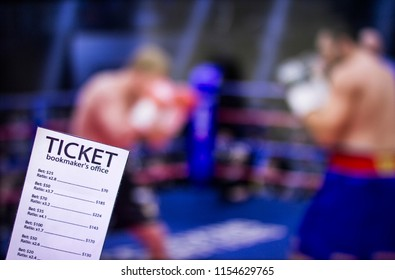 Bookmaker ticket on the background of the TV on which show boxing, sports betting, ring