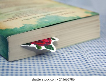 Bookmark in book on blue white checkered table cloth