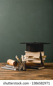 books, academic cap, notebooks, scroll, pencils on wooden surface isolated on grey