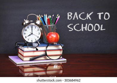 Books, apple, alarm clock and pencils on wood desk table. Text back to school on black board concept