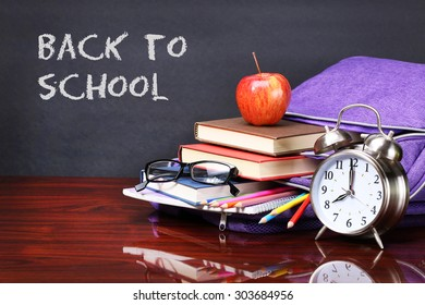 Books, apple, backpack, alarm clock and pencils on wood desk table. Text back to school on black board concept