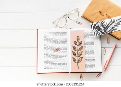 Books with bookmarks, glasses and stationery on light wooden background