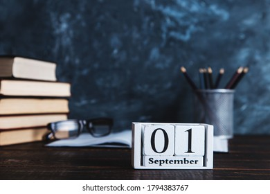 Books, calendar, notebooks, pencils, glasses and cup of coffee, against the background of a chalkboard. Concept for knowledge day. Copy space.