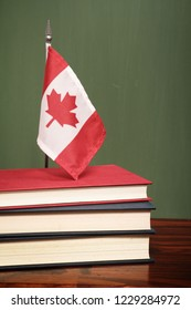 Books and Canadian flag in front of a green chalkboard