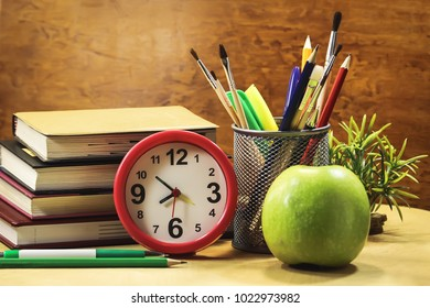 books, clocks, apple, stationery on a wooden table. Concept of education.