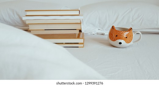 Books and coffee on white bed
