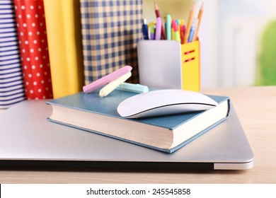 Books, computer mouse and pieces of chalk on wooden table and light background