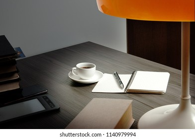books and cup of coffee on a writing desk, lighted up by a reading-lamp with an orange lamp-shade