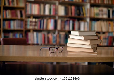 Books and eyeglasses on wooden desk in library, bookshelfs in background.