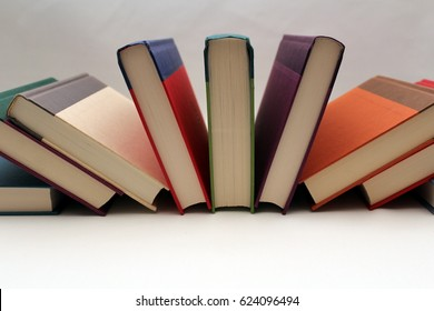 BOOKS FANNED ON SIDE ON WHITE BACKGROUND