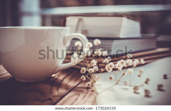Books, flowers and white cup on wooden table
