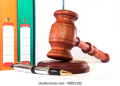 Books, folders, pen and gavel on a white background