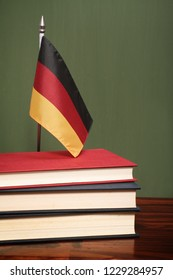 Books and German flag in front of a green chalkboard