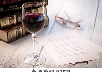 Books, a glass of wine and poetry on the old wooden table. Shakespeare Poems