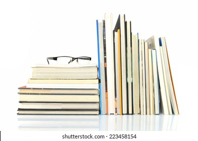 Books with glasses on white background
