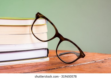Books and glasses on a wooden table, on green background