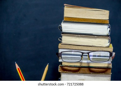 Books , glasses and pencil with chalkboard background. Education concept.