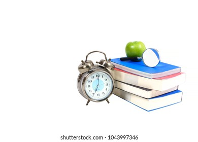 Books , green apple , magnifying glass and traditional wind-up (keywound), spring-driven alarm clock isolated on white background