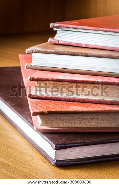 Books hardcover color produced by hand in a medical library, arranged on a wooden table.