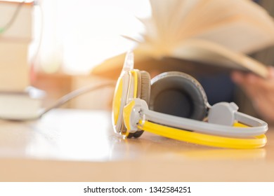 Books and headphones as audio books concept on  high school or university library background