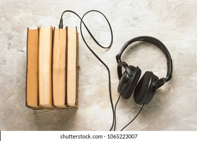 Books and headphones connected to them on a white stone background. Concept Audiobooks.